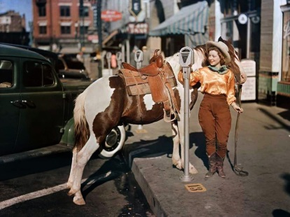 A cowgirl puts a nickel in an El Paso parking meter to hitch her pony, October 1939