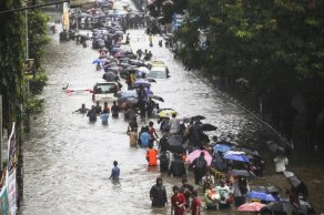 MUMBAI, INDIA - AUGUST 29: Indian people wade along a flooded street as car get stuck during heavy rain in Mumbai on August 29, 2017. Heavy rain brought India's financial capital Mumbai to a virtual standstill on August 29, flooding streets, causing transport chaos and prompting warnings to stay indoors. Dozens of flights and local train services were cancelled as rains lashed the coastal city of nearly 20 million people. (Photo by Imtiyaz Shaikh /Anadolu Agency/Getty Images)